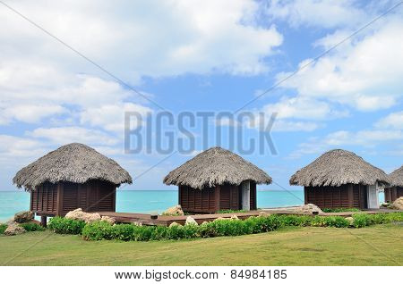 Three bungalows In Front Of Turquoise Sea.