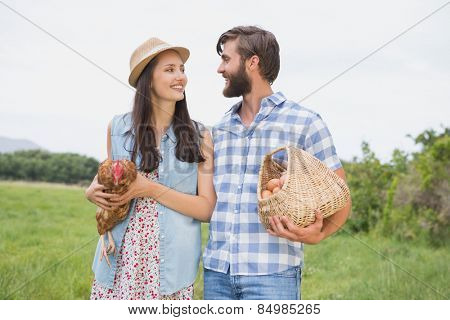 Happy farmers holding chicken and eggs on a sunny day