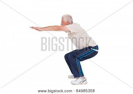 Senior man doing a squat on white background
