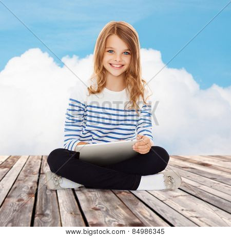 education, technology, childhood and people concept - happy little student girl with tablet pc over blue sky and cloud background