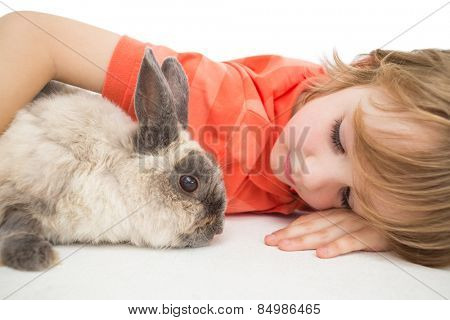 Cute boy lying arm around bunny on white background