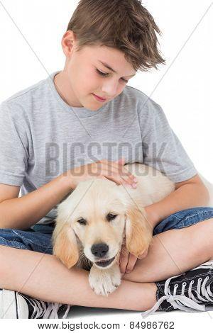 Loving boy stroking dog while sitting over white background