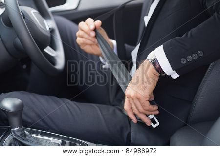 Businessman putting on his seat belt in his car