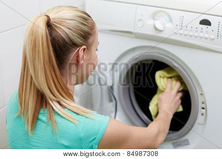 people, housework, laundry and housekeeping concept - happy woman putting laundry into washing machine at home