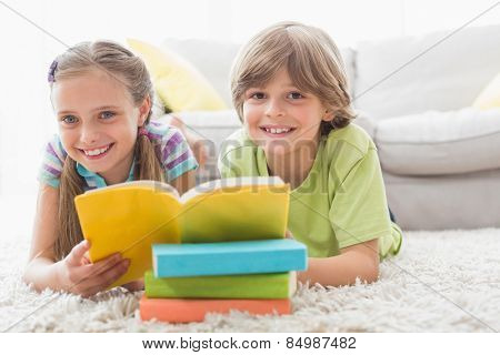 Portrait of happy siblings reding book while lying on rug in living room