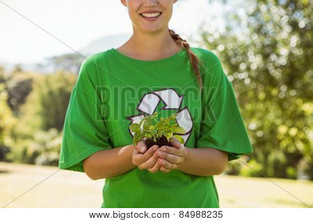 Environmental activist showing a plant on a sunny day