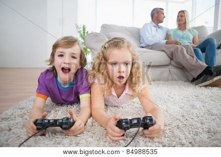 Brother and sister playing video game while parents sitting on sofa at home