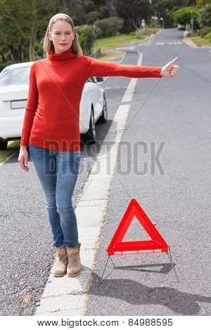 Pretty woman hitch hiking in the street