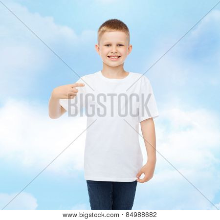 advertising, gesture, people and childhood concept - smiling boy in white t-shirt pointing finger at himself over cloudy sky background