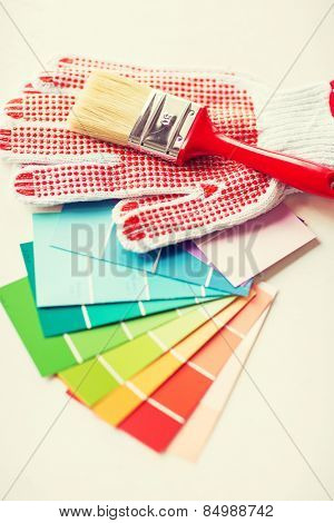 interior design and home renovation concept - paintbrush, gloves and pantone samplers