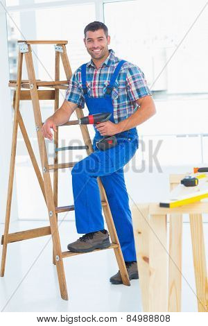 Full length portrait of confident carpenter with power drill climbing ladder at construction site