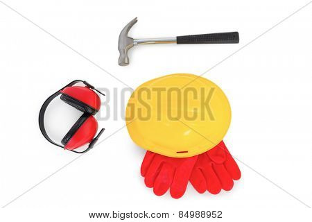 Yellow hardhat with protective gloves, earmuffs and hammer on white background