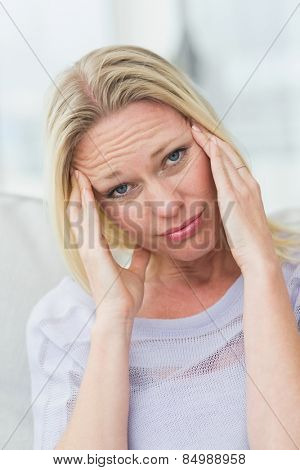 Portrait of upset woman rubbing her temples in living room