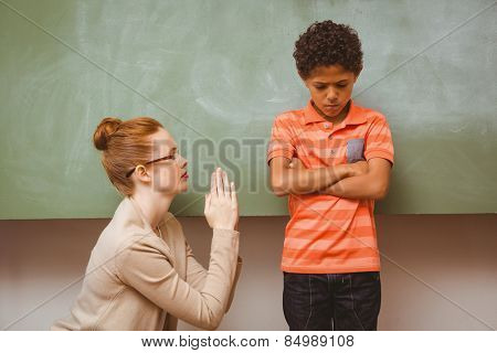 Female teacher apologizing boy in the classroom