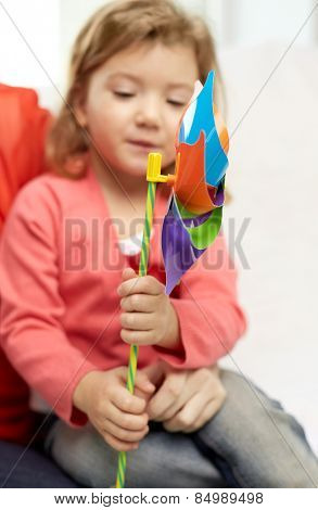 family, children, future and happy people concept - happy little girl with mother holding pinwheel toy at home