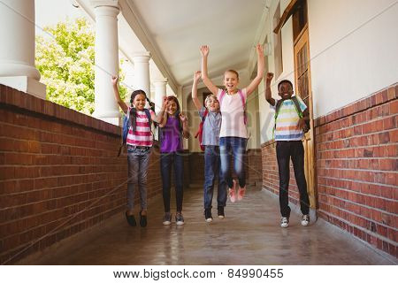 Full length portrait of school kids running in school corridor
