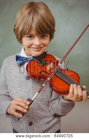 Portrait of cute little boy playing violin in classroom