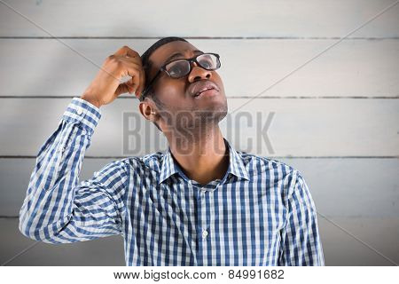Young businessman thinking scratching head against painted blue wooden planks