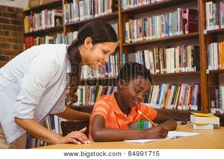 Portrait of teacher assisting little boy with homework in the library