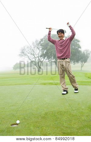 Excited golfer cheering on putting green at the golf course