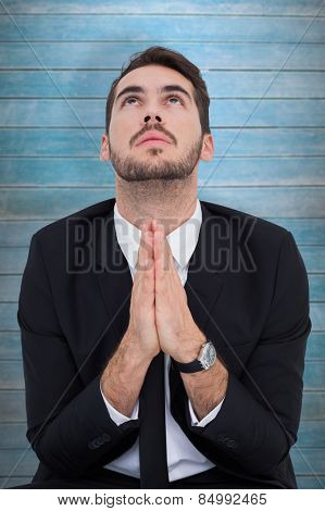 Elegant businessman with hands together prying against wooden planks