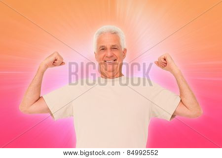 Senior man flexing his arms against abstract background