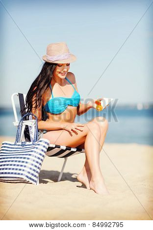 summer holidays and vacation - girl applying sun protection cream