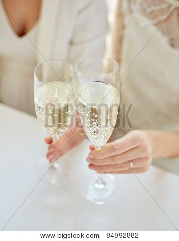 people, homosexuality, same-sex marriage, celebration and love concept - close up of happy married lesbian couple hands holding and clinking champagne glasses