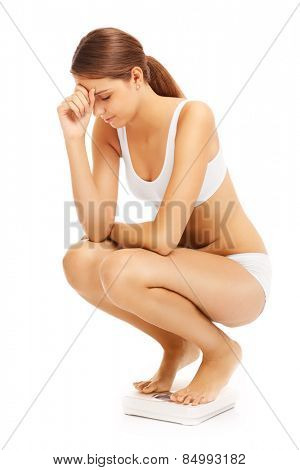 A picture of a sad woman on a bathroom scales over white background