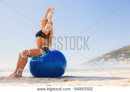Fit blonde sitting on exercise ball at the beach against fitness interface