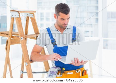 Repairman using laptop by step ladder in bright office