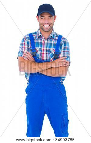 Portrait of smiling male handyman in coveralls standing arms crossed over white background