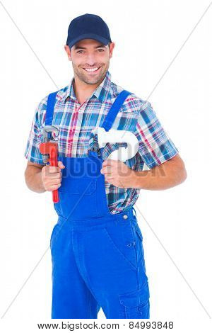 Portrait of happy male plumber holding monkey wrench and sink pipe on white background