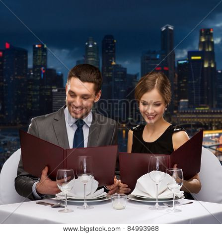 food, holidays and people concept - smiling couple with menus at restaurant over night city background