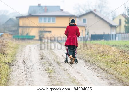 Woman With Stroller On Sandy Road