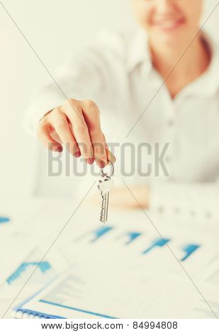 business, banking, real estate concept - woman hand holding house keys
