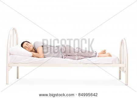 Happy young man sleeping in a bed isolated on white background
