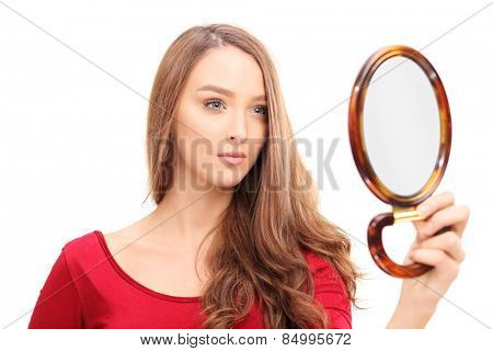 Studio shot of a gorgeous woman looking herself in a mirror isolated on white background