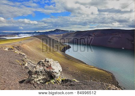 The blue lake in a crater of the cooled-down volcano. Coast of the lake are put from a red rhyolite. Iceland in July