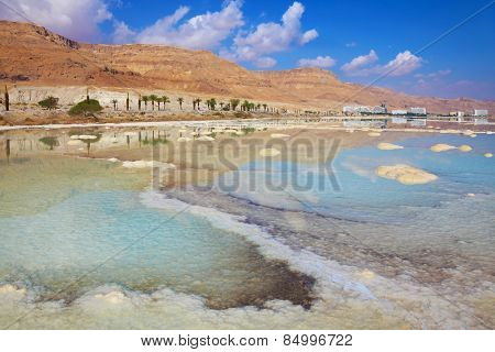Israeli coast of the Dead Sea. The path from salt picturesquely curls in salty water. Hotels are reflected in the sea ashore