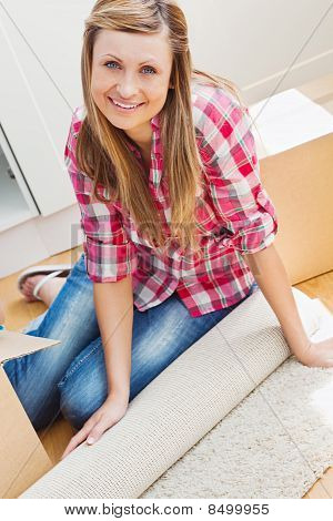 Smiling Woman Unpacking A Box On The Floor