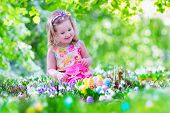 stock photo of egg whites  - Adorable curly toddler girl in a pink summer dress playing with Easter eggs during egg hunt in a sunny garden with first white spring flowers - JPG