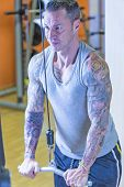 picture of pulley  - young man making pulley pushdown standing  - JPG