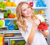 picture of strawberry blonde  - Portrait of cute blond woman standing near open refrigerator full of fruits and vegetables and eating fresh red ripe strawberries - JPG