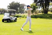 picture of take off clothes  - Female concentrating golfer teeing off on a sunny day at the golf course - JPG