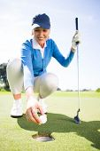 pic of kneeling  - Smiling lady golfer kneeling on the putting green on a sunny day at the golf course - JPG