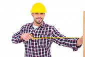 image of handyman  - Handyman using measure tape on wooden plank on white background - JPG