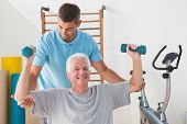 stock photo of studio  - Senior man working out with his trainer in fitness studio - JPG