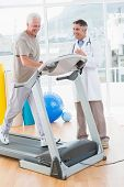 foto of treadmill  - Senior man on treadmill with therapist in fitness studio - JPG