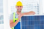 picture of handyman  - Portrait of happy handyman with solar panel in bright office - JPG